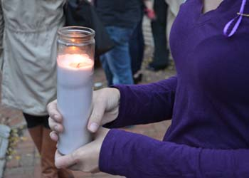 Students and faculty gather for a candle vigil for victims of sexual assault and violence