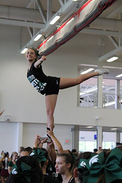 Cheerleading team members doing a lift