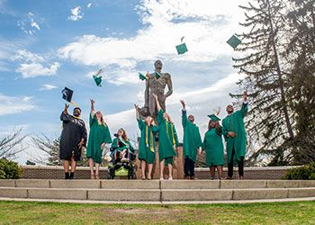students celebrate graduation at the Spartan statue