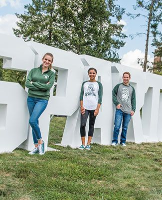 MSU students pose in front of the SPARTANS block text installation