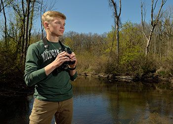 Evan Griffis observes birds as part of his research project