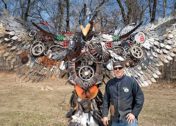 Joe Butts, '98 (Arts and Letters), and his Phoenix sculpture.