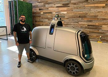 Marshall Mendoza, B.A., '10, Engineering, poses with his company's autonomous vehicle