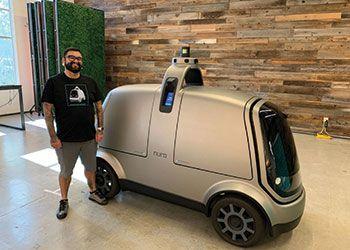 Marshall Mendoza, B.A., '10, Engineering, poses with his company's autonomous vehicle