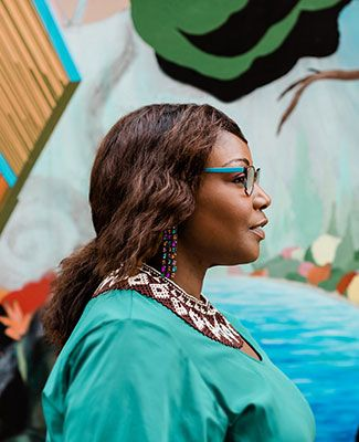 kinitra brooks posed in profile in front of a colorful mural