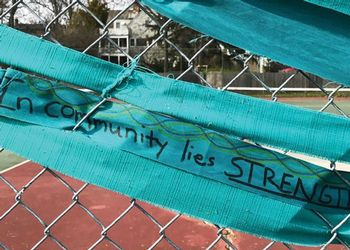 Teal ribbon  on a chain link fence with a message
