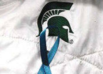 teal ribbon pinned to a jacket with a spartan logo