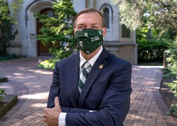 President Samuel L. Stanley Jr., M.D. wears a Spartan mask in front of Beaumont Tower.