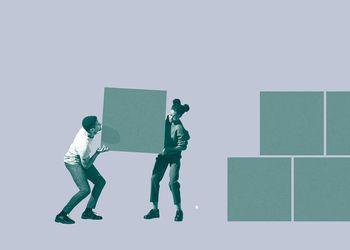 Two individuals lift figurative block