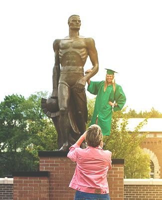 Graduate taking a photo with Sparty