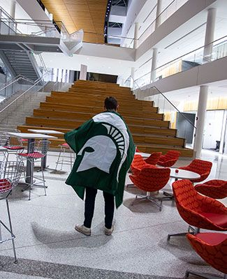 student in spartan helmet flag standing in front of Minskoff steps