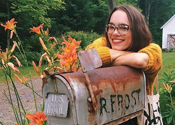 Leila Chatti poses with the mailbox of Robert Frost.