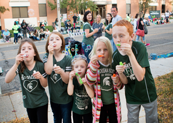 Children blowing bubbles at the MSU Homecoming Parade