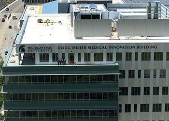 Norm Beauchamp, Doug Meijer, and other stakeholders stand on the roof deck of the new medical innovation building in downtown grand rapids.