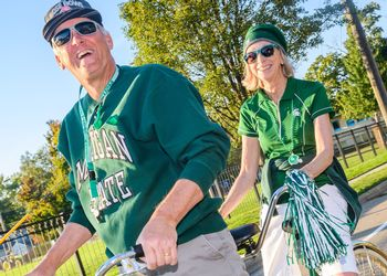 Two Spartans in Spartan gear on a tandem bicycle in the parade