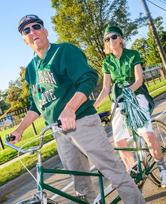 Two Spartans on a tandem bicycle decked out in Spartan gear