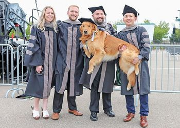 veterinary medicine grads with a dog
