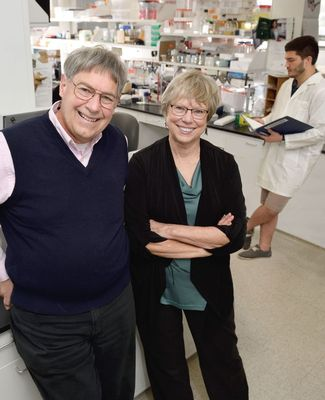Dan and Karen Friderici pose in a lab with a student in a labcoat working in the background