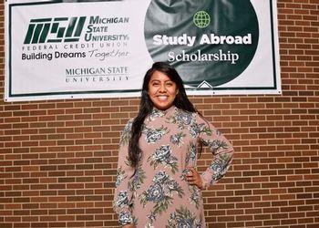 Selena Huapilla-Perez with the MSUFCU Study Abroad banner
