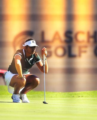 A golfer lines up her shot with the Lasch building in the background