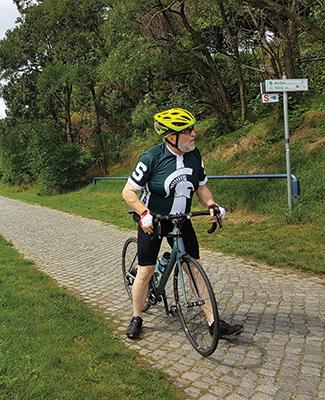 Alumnus George Melnik rides his bicycle