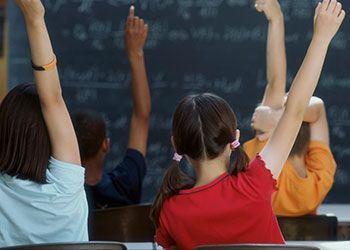 children in a classroom raising hands