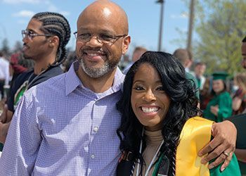 A successful graduate poses with her father