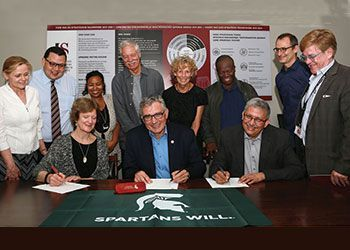 leaders from universities sign a paper at a table with a spartan flag