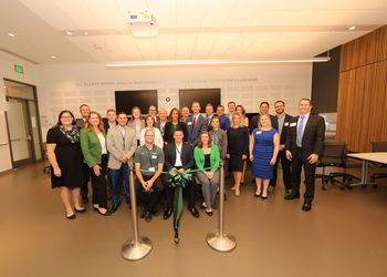 Students and faculty pose at the ribbon cutting ceremony for the new classroom space