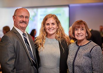 Carol and Joe Vermeesch stand on either side of Kendall Austin, a student in the College of Nursing