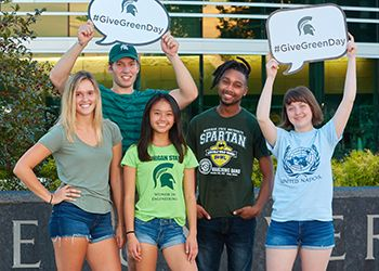 MSU Students holding #GiveGreenDay signs