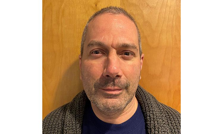 portrait of Dan Furton, wearing a blue shirt and gray sweater
