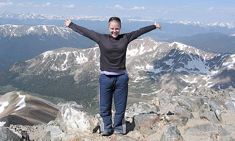 photo of Renee Cherry standing on a mountaintop with other mountains in the background. She is holding her arms out wide.