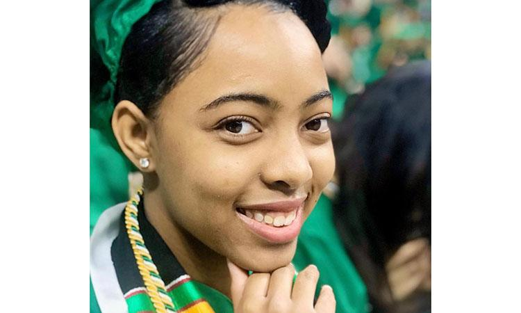 portrait of Sheritha Rayford, wearing her MSU green graduation cap and gown.