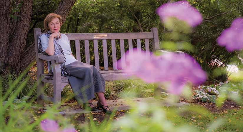 judy delapa poses on a bench in one of MSU's gardens