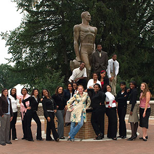 students pose around The Spartan statue