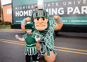 Sparty with a young child.
