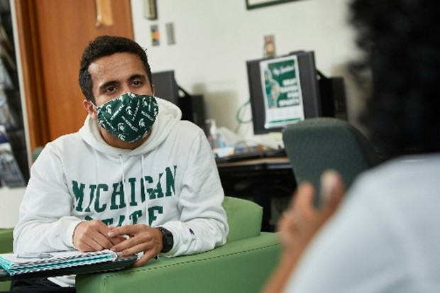 Photo of a student wearing a mask in a study lounge.