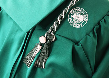 MSU green cap and gown and a graduation tassel.