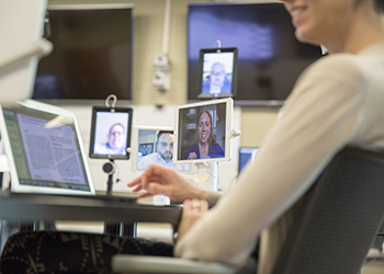 Individuals connecting over tablets for a meeting