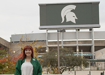 A student in front of Spartan stadium