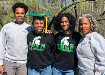 Mom and dad posing with their two MSU graduate daughters