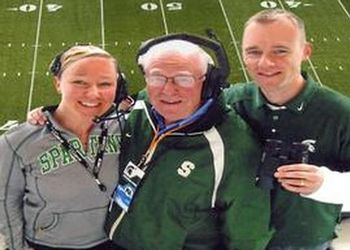 Terry Braverman (center) in the Spartan Stadium public address booth with his assistants for the day, daughter Lindsey and son Christopher.