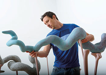 MFA student Joe Wilkinson carefully places a coiled clay sculpture, painted blue, atop flesh-toned wooden spikes as part of his art installation.