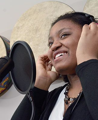 A young girl wearing a headset sings into a microphone in a recording studio. She is smiling, wearing a black sweater and a beaded necklace.