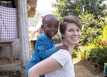 Clare O'Kane smiles and gives a piggyback ride to a young Tanzanian boy, who is also smiling.