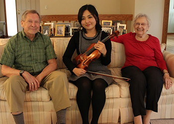 Photo of MSU student violinist Sin Young Kim with donors Ron and Helen Priest