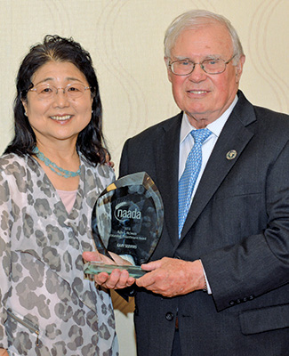 Photo of Eiko and Gary Seevers holding the 2016 Outstanding Philanthropist Award from the National Agricultural Alumni and Development Association