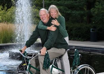 Cliff and Sue Haka pose with their bicycle in front of the MSU Library fountain