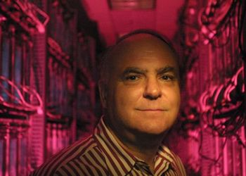 John R. Koza wears a striped shirt and stands in a pink-lighted hallway full of computer circuit boards.